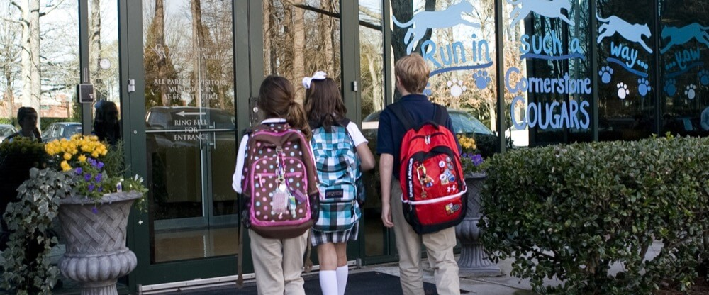 students walking into school with backpacks