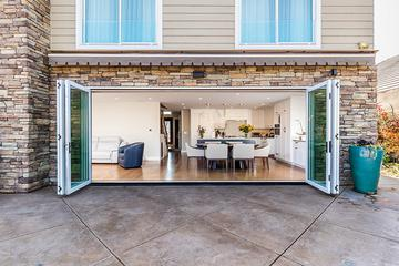 large white accordion glass doors opened from center looking into modern dining room