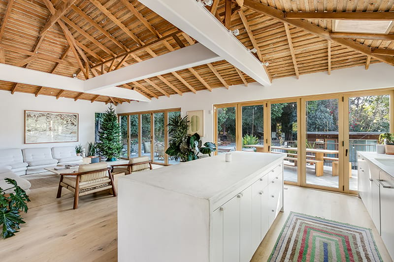 white kitchen with wood folding glass doors and high exposed wood ceiling