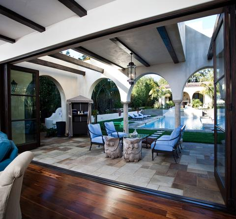 Huge bifold doors open to a patio and pool in a Mediterranean style home.