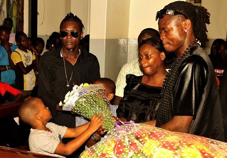 Chameleone's son's laying a wreath on the casket