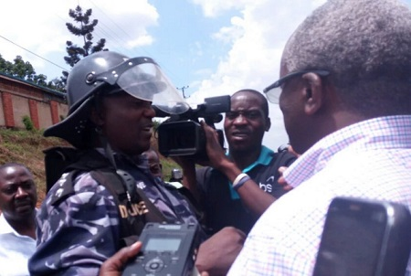 Former Premier explaining to a cop why he should visit FDC's Besigye