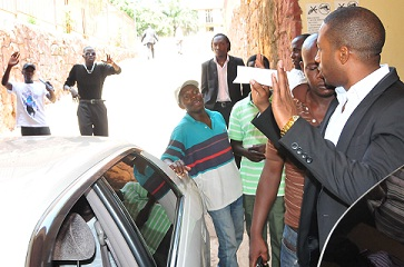 Meddie waves to some of his colleagues who were outside the court