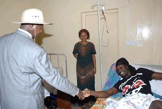 The President shaking Bebe Cool's hands as Zuena looks on