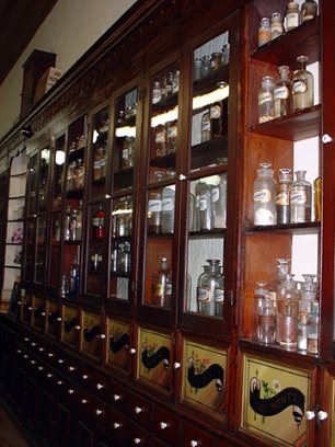 ornate pharmacy cabinets with hundreds of bottles, vials, and boxes
